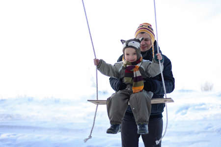 Adult father helps his smiling toddler boy in funny hat to fly on a swing against the white field at winter walk outdoors, winter family lifestyle 免版税图像