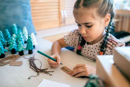 Cute girl preparing DIY gifts and signing tags to parents and family for Christmas, a green cone as if it is small toy pine tree, tags and festive boxes, handmade presents, zero waste holidays