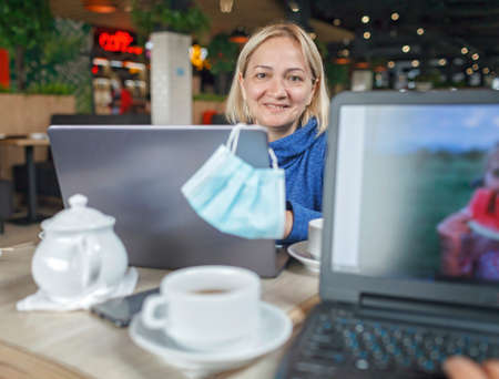 Businesswoman sitting in modern cafe with portable computer and drinking coffee during online meeting, social distance, new reality lifestyle
