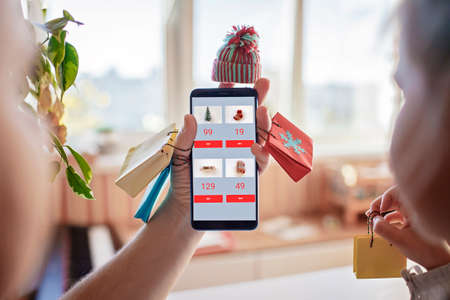 Online shopping concept. Handsome father with his cute daughter having fun with smartphone wearing knitted hat and with tiny shopping bags during their online shopping at home, black Friday and sales 版權商用圖片