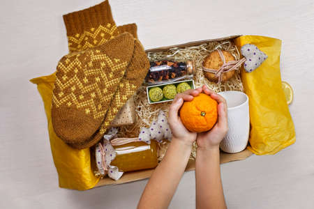 Cute girl packing festive care box with tea, honey, cookies and knitted wool socks for grandmother. Personalized care box during lockdown, support and surprise for family and friends on Christmas 版權商用圖片
