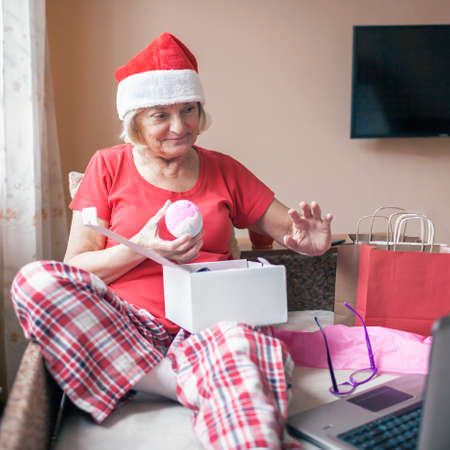 Safe online Christmas celebration. Senior woman in Santa red hat giving present to her family virtually with internet and notebook. Video call. Stay home, distant holiday, emotional indoor lifestyle