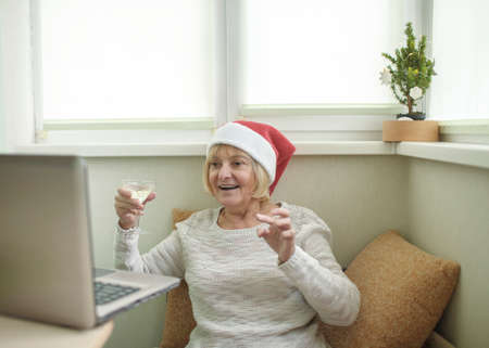Safe online celebration. Senior woman holding a glass of wine and celebrating Christmas with her family virtually via internet and notebook at home. Video call. Distant holiday, indoor lifestyle Imagens