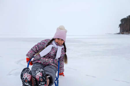 School age girl have fun on the frozen lake and enjoying a sleigh ride. Winter, silence and wild nature, active winter weekend, seasonal outdoor activities, happy family lifestyle, copy space