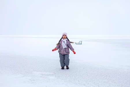 School age girl have fun on the frozen lake and enjoying winter season. Winter, silence and wild nature, active winter weekend, seasonal outdoor activities, happy family lifestyle, copy space