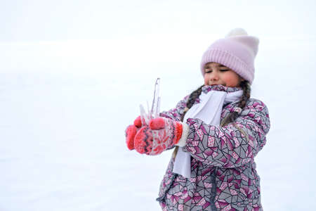 School age girl have fun and gathering a winter bunch of icicles, enjoy winter season and taste them. Winter, wild nature, active weekend, seasonal outdoor activities, happy family lifestyle