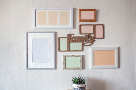 White wall with set of different empty vertical and horizontal picture frames to create family photo gallery on the wall, to capture a moment, mockup template on the white background, lifestyle Banque d'images