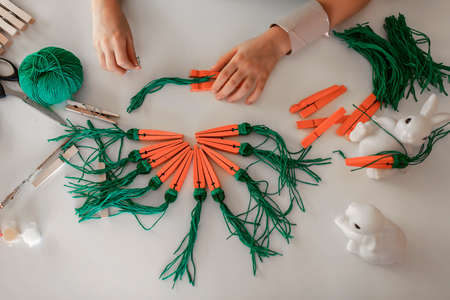 Elementary school girl doing carrot with wooden clothes pins for Easter celebration looking video on laptop, online workshop, kid at-home activity, creativity and distant education, holiday decoration