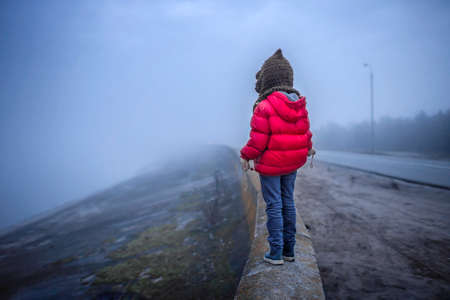 Cute 7 years old girl walking alone on the road in spring foggy day, uncertainty and looking forward concept, lifestyle outdoor. Stress, depression and psychological problem of isolation