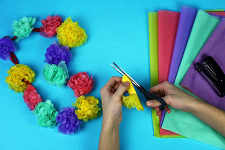 Young boy doing by himself Hawaiian garland with paper flowers, party decoration, vacation and travel concept, DIY