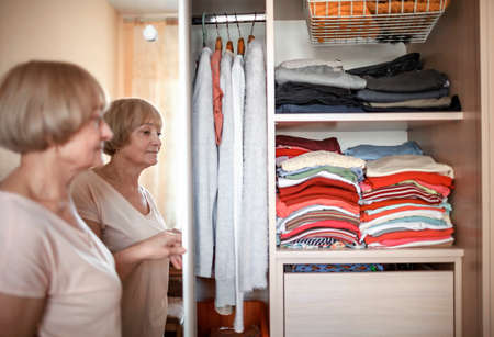 Senior woman choosing outfit from wardrobe closet with clothes and home stuff. Cleaning, organizing and order in the closet Stockfoto