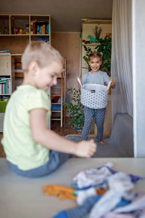 Household chores for children. Kids cleaning their room, sorting dry socks and arranging them into personal baskets with fun, they turn cleaning into the game. Everyday routine, lifestyle