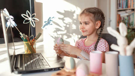Girl demonstrating DIY flowers, wreath, eggs and greeting with spring holidays her family via internet, online Eater celebration, zero waste, craft for kids, new normal and social distance