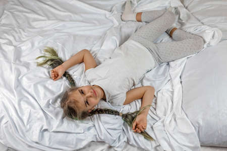Cute awaking girl in white clothes with two braids lying on the bed in bedroom in the morning, happy family concept, healthy lifestyle and sleep care