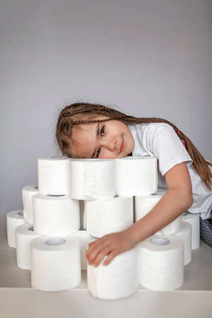 A pretty girl stocking up the heap of toilet paper over white background, prepare for self-isolation during lockdown, healthcare and personal hygiene, studio shot