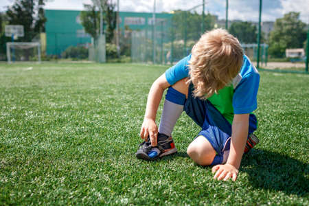 Young soccer player looks at the boots torn during the game on the football field, hard training, sport, outdoor lifestyle