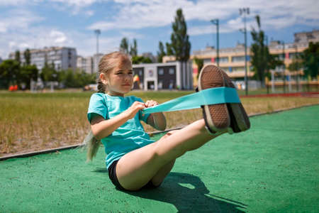 Cute preteen girl making exercises with fitness resistance band at public sportsground in the city, wellness and fitness, sport and recreations, healthy lifestyle Stock Photo