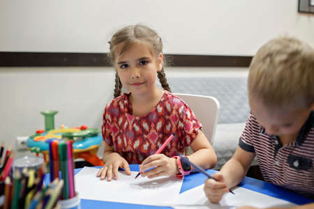 A lefty girl and righty boy writing at the same desk and nudge each other with elbows, international left-hander day celebration, only lefties understand Standard-Bild