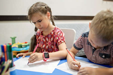 A lefty girl and righty boy writing at the same desk and nudge each other with elbows, international left-hander day celebration, only lefties understand