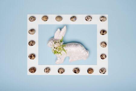 white handmade rabbit in white frame and eggs on blue background