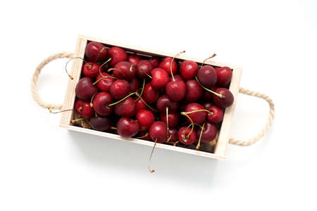 Wooden box full of dark red sweet cherries isolated on white background flat lay