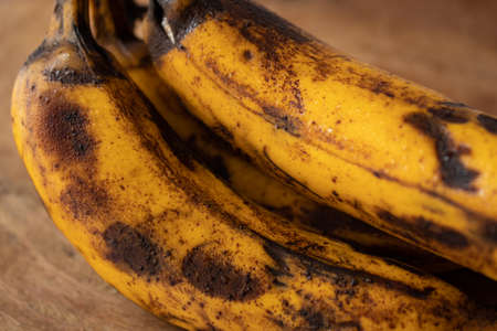 Close-up of bunch with overripe bananas on wooden board