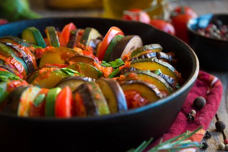 Homemade ratatouille made with sliced vegetables: zucchini, tomatoes and eggplant.