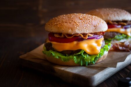 Hamburger with cheese, bacon, tomato and lettuce on dark wooden background