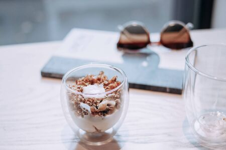 Muesli in a glass. Dessert in a cup and on a light background in cold shades. Diet breakfast. Diet food. Zdjęcie Seryjne
