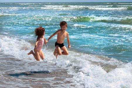 Ragazza e ragazzo stanno saltando su una riva del mare