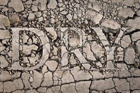 """emaciated: The word """"dry"""" written on the dried ground Stock Photo"""