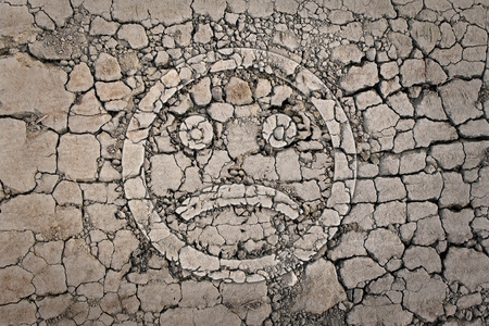 Sad smiley on the cracked, dried ground Stock Photo