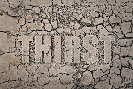 """emaciated: The word """"thirst"""" written on the dried ground Stock Photo"""