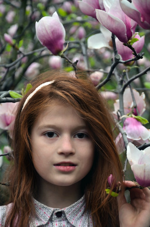 There are flowering magnolias an red-haired girl ten ears old