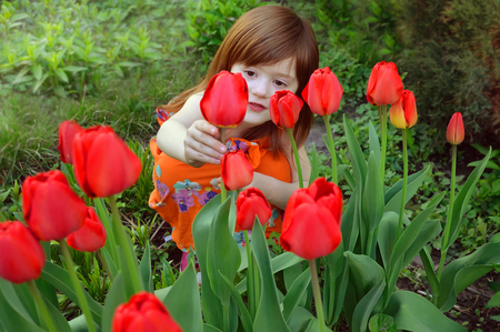 babygirl: The little girl sits among flowering tulips and looks at one of the flowers Stock Photo