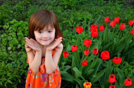 The little girl stands among red flowering tulips