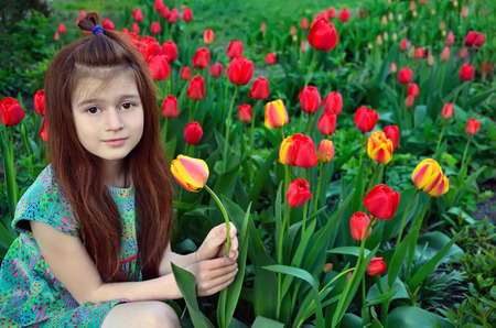 babygirl: The red-haired girl sits among flowering tulips