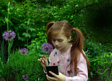 selfy: A girl is taking the selfy with a smartphone in a garden
