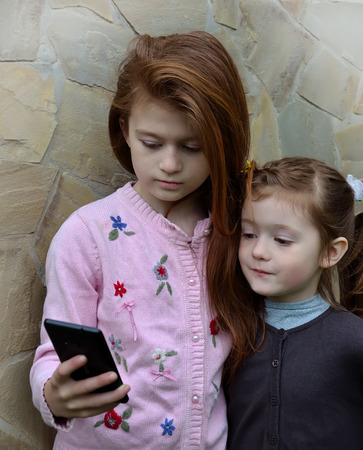 selfy: Two girls are taking the selfy with a smartphone