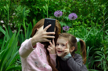 selfy: Two girls are taking the selfy with a smartphone in a garden