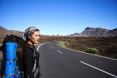 wild canary: Young Female Traveler hitchhiking on the volcano Teide, Tenerife, Spain Stock Photo