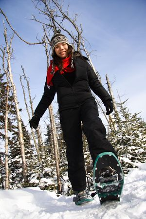 snowshoeing: Young woman snowshoeing in pine forest near Baie Saint-Paul, Quebec, Canada