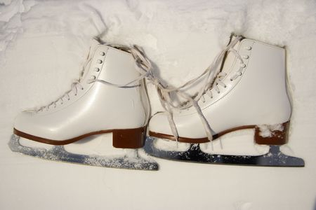 wintersports: Closeup of figure skating ice skates lying in the snow outdoors