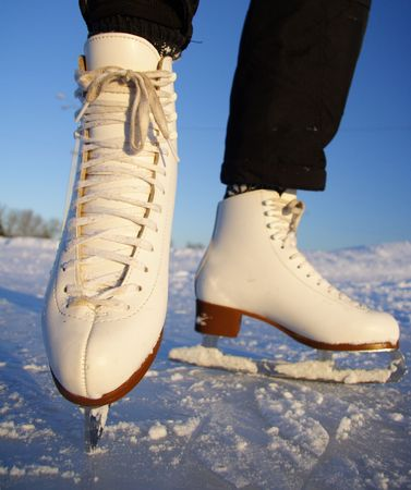 wintersports: Closeup of figure skating ice skates in action outdoors