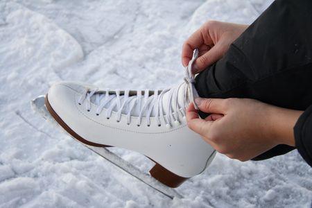 schaatsen: jonge vrouw koppelende veters op figuur schaatsen op openlucht ijsbaan