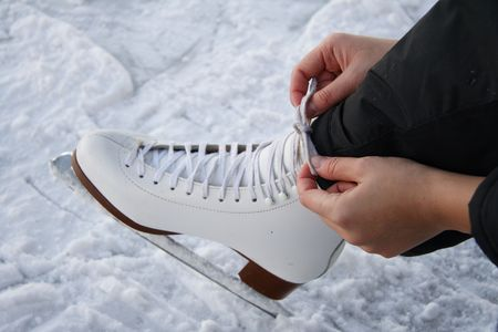 ice skate: young woman tying laces on figure skate on outdoor rink