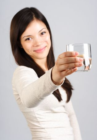 Have a glass of water! Beautiful young woman offering a glass of water. Glass is sharp, face is out of focus. Stock Photo - 4441058