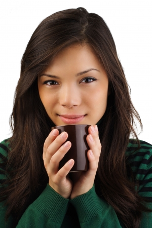 Beautiful young eurasian woman enjoying a warm drink.  photo