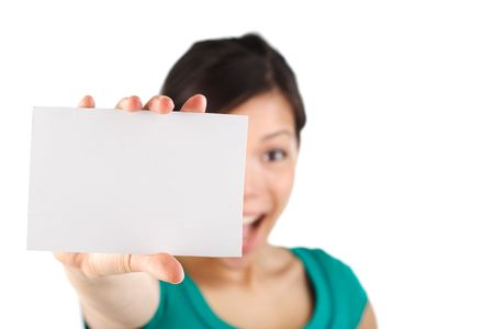 Very excited young woman holding a blank card. Card in focus, woman out of focus. Isolated on white. photo
