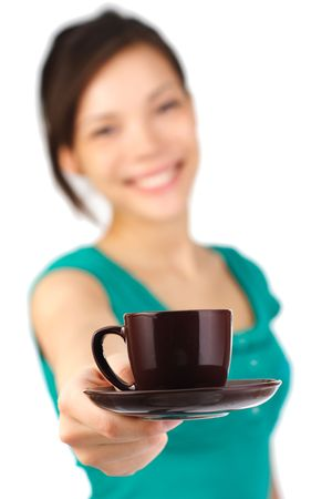 Beautiful young woman with big smile serving an espresso. Cup is sharp, model out of focus. Isolated on white. photo